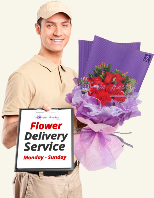 Flower delivery man holding a red rose bouquet